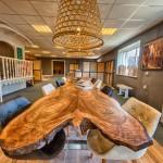 De enorme notenhouten tafel is het middelpunt van onze showroom.a