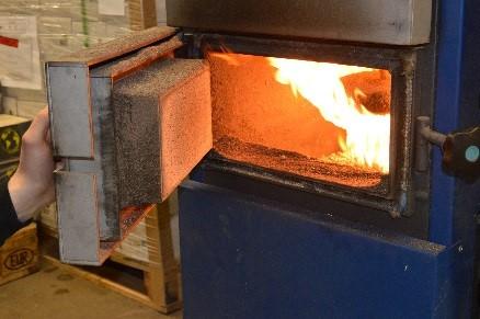 De pellets gaan de oven in. Door het buizensysteem aan de oven wat het hele pand doorgaat, wordt het gehele pand verwarmd